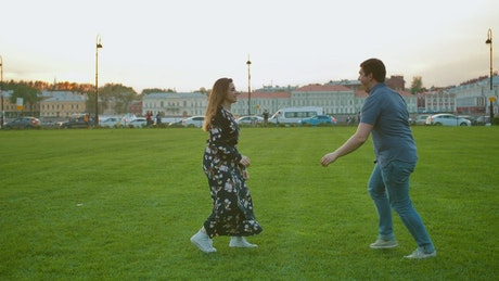 A cute couple playing on the grass