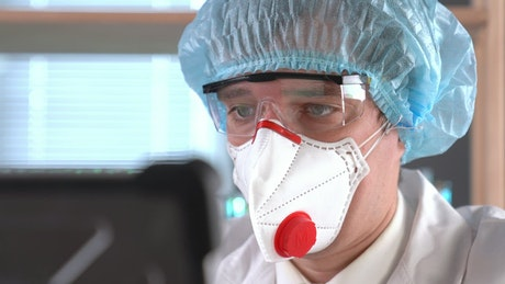 A doctor wearing a face mask and protection glasses