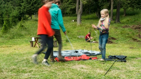 A family setting up a camping tent