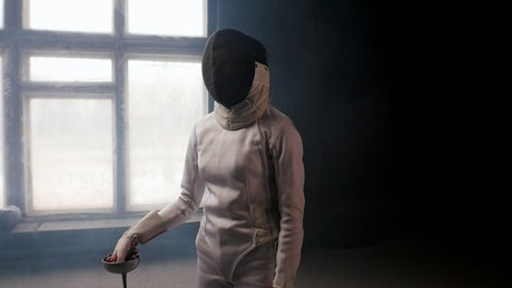 A fencer putting the sword behind the shoulders