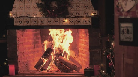 A fireplace lit at Christmas time