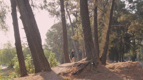 A girl and a boy jogging through a forest
