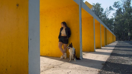 A girl and a dog standing in front of a wall