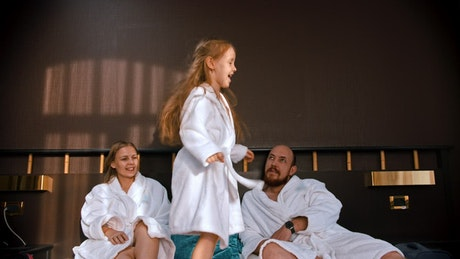 A girl jumping on the bed in a bathrobe