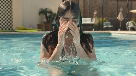 A girl moments after diving into a pool