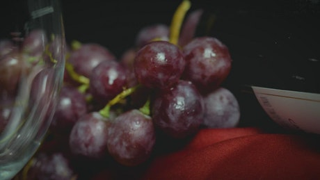 A glass, a bunch of grapes, and a bottle of wine