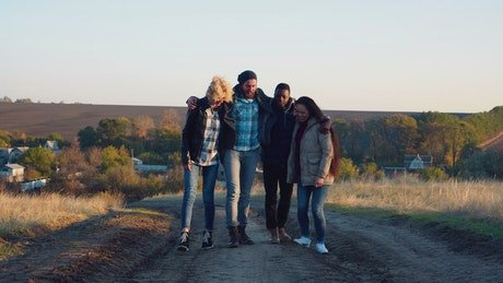 A group of friends hugging and walking on a path