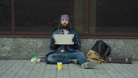 A homeless guy holding a sign