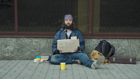 A homeless man begging sitting on the street