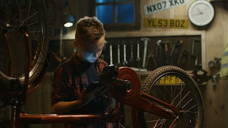 A little boy is repairing his bike with tutorial