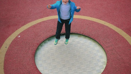 A little boy jumping on the trampoline at the playground