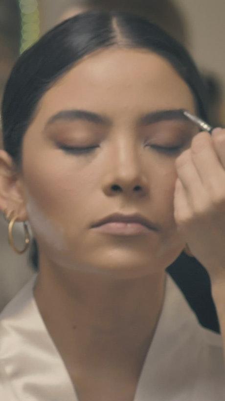 A makeup artist with face mask putting on makeup