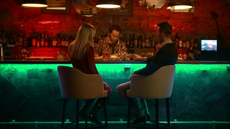 A man and a woman having a date at a bar counter