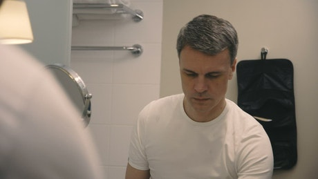 A man brushes his teeth in the bathroom