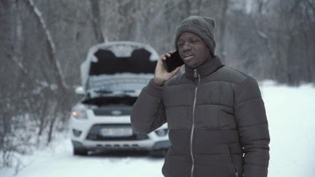 A man calling car insurance for a broken car