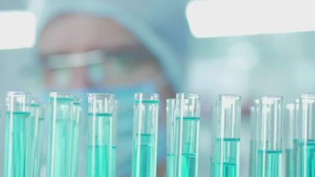 A man droping liquid on lab tubes