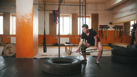 A man hitting a tire with a mallet in the gym
