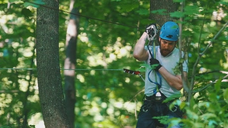 A man in a security helmet on a rope adventure in the forest
