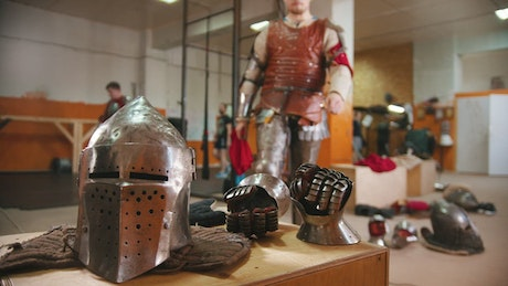 A man in the dressing room putting on the armor iron gloves