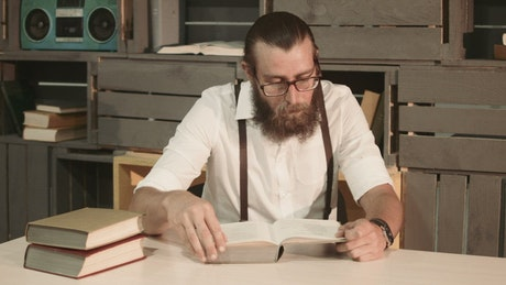 A man is reading a book on the table