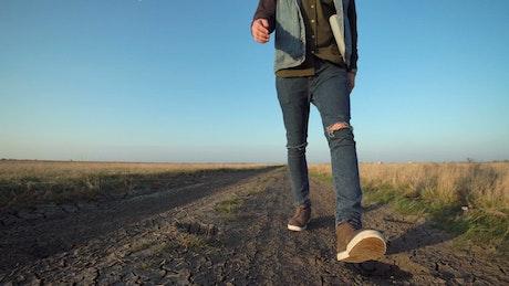 A man is walking on rural path