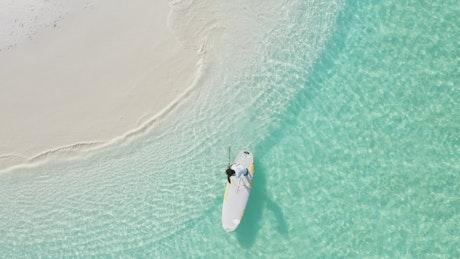 A man paddling on a board near the seashore