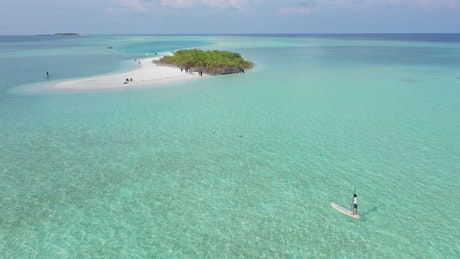 A man paddling on a board to get to a little island