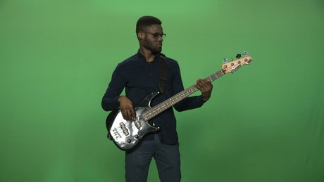 A man playing a black guitar and a greenscreen