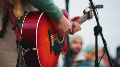 A man playing the guitar on stage in a festival