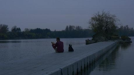 A man reading a book on a concrete pier