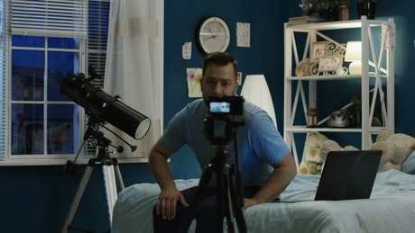 A man recording a video on the bedroom
