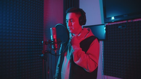 A man singing in the recording studio