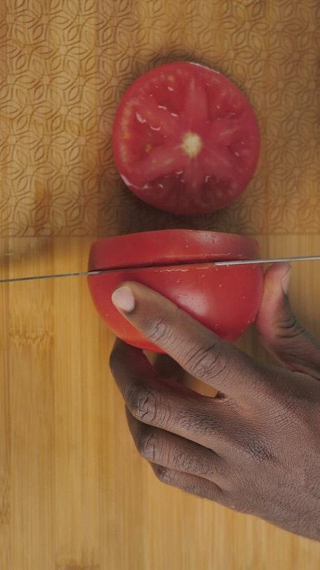 A man slices a tomato