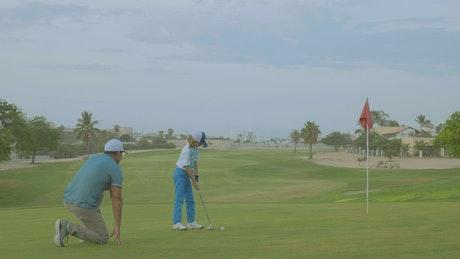 A man teaching his son how to play golf