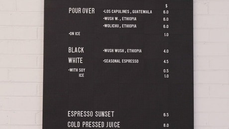 A man walking by the side of a coffee shop menu