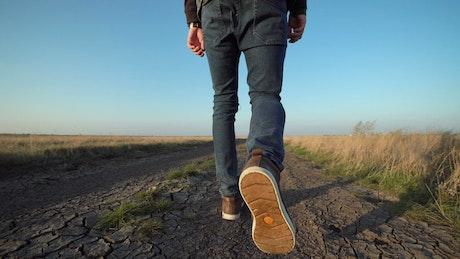 A man walking on a dirt road