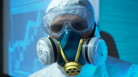 A man wearing a biohazard suit and a mask