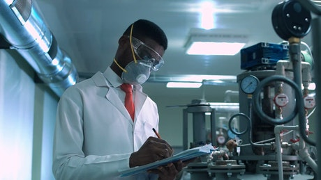 A man with a face mask checking laboratory