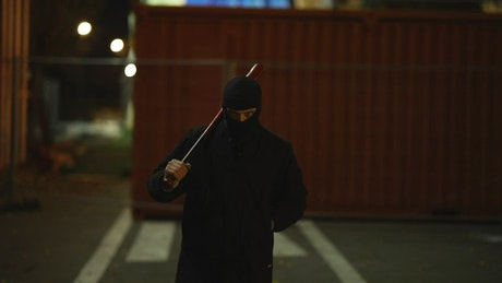 A menacing gangster walking with a baseball bat