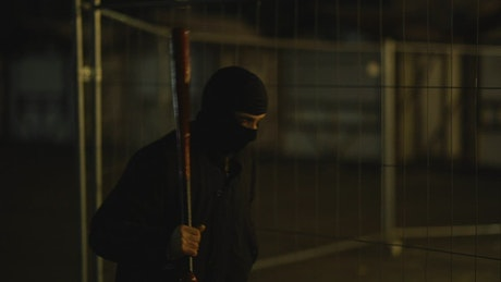 A menacing gangster  with a baseball bat