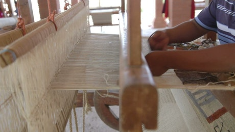 A Mexican person weaving a cloth on a large loom