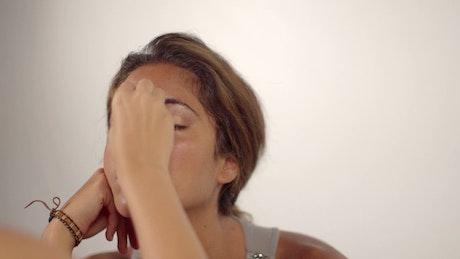 A model having her makeup applied