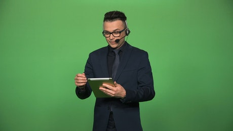 A newscaster with tablet and headset