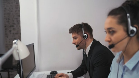 A pair of employees working in a call center