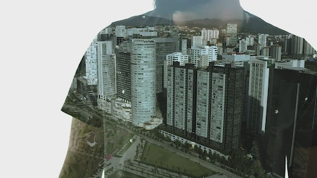 A person crossing his arms and a city with tall buildings