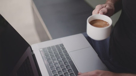 A person drinking coffee while using a laptop