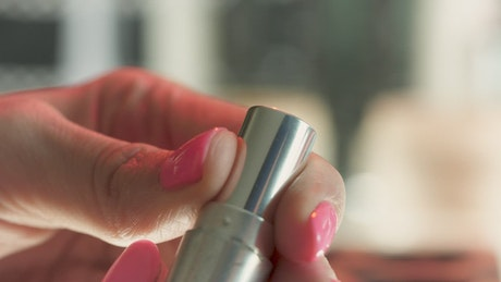 A person opens a pink lipstick