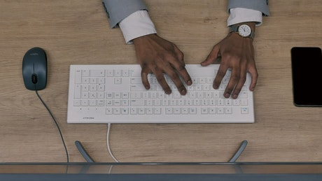 A person's hands typing on a wifi keyboard