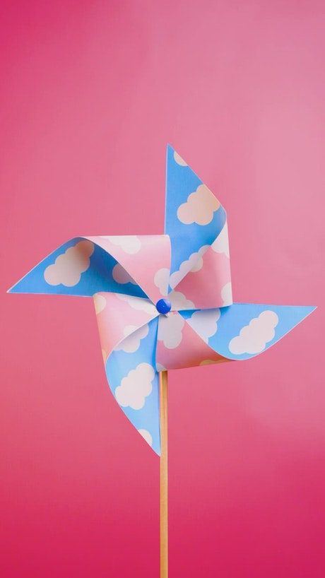 A pinwheel spinning on a pink background