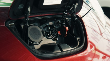 A red electric car being charged